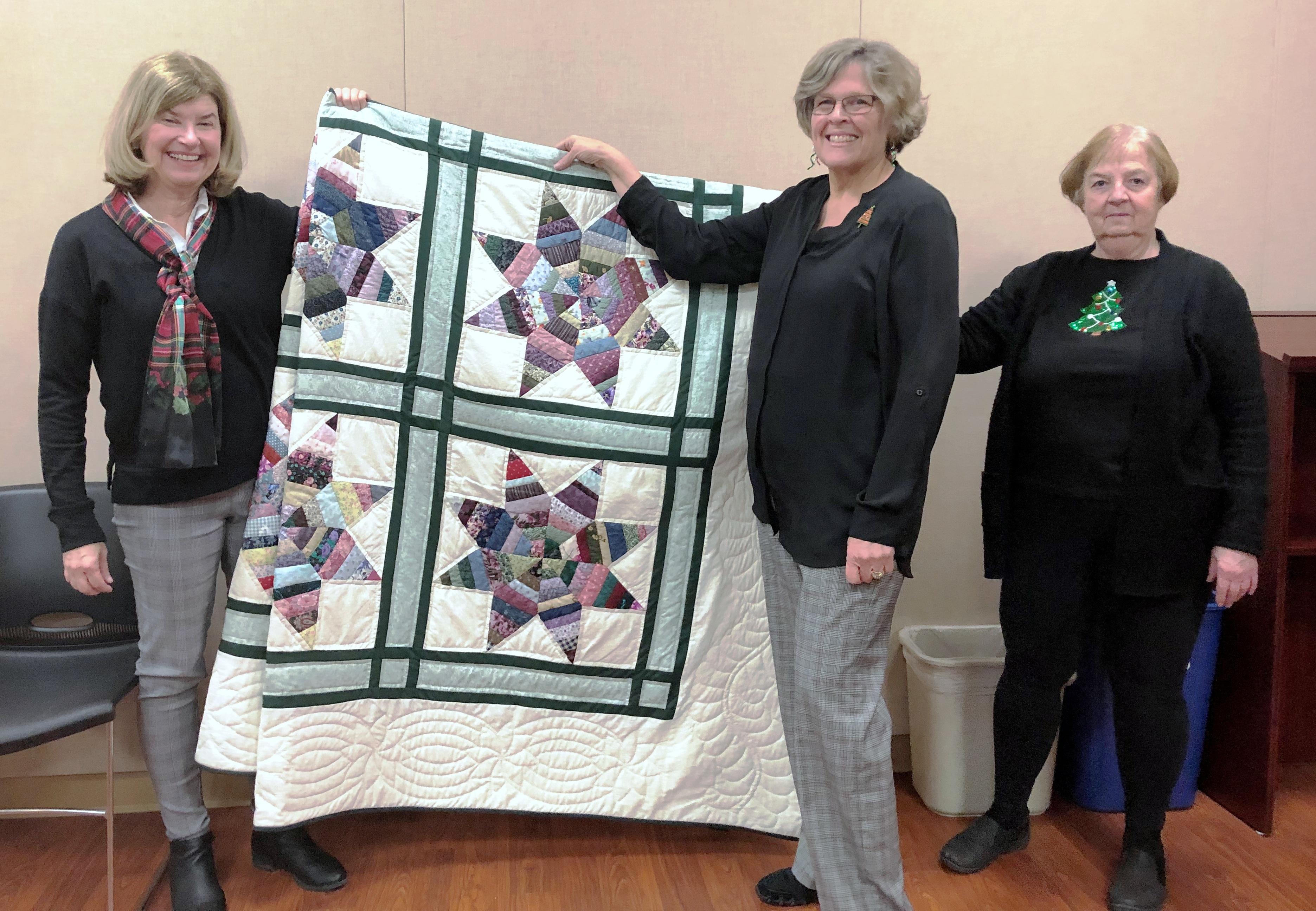 Ellen Hair and Barb Allen present the quilt to winner Susan Renninger